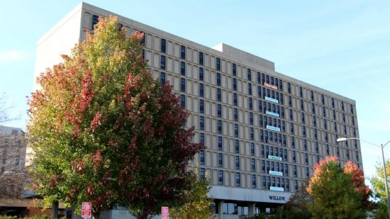Iowa State University residence hall building with tree in foreground and blue sky in background