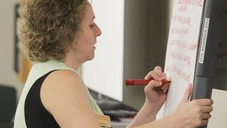 Krisdeena Jansen from university human resources writing on an easel during a listening session