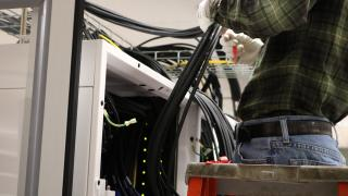 A technician installing a portion of the new High Performance Computing (HPC) cluster