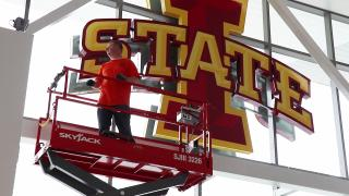 Employee on a scissor lift installing new access points at Jack Trice Stadium